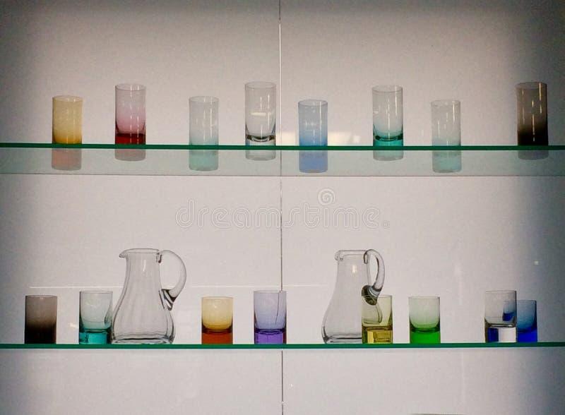 Exponeringsglaskoppar på två Glass hyllor arkivfoton