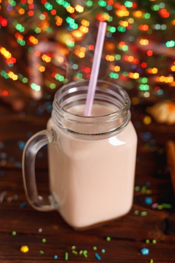 Exponeringsglaskoppen av varm kakao med mj?lkar, kanel- och sugr?rr?ret royaltyfri bild