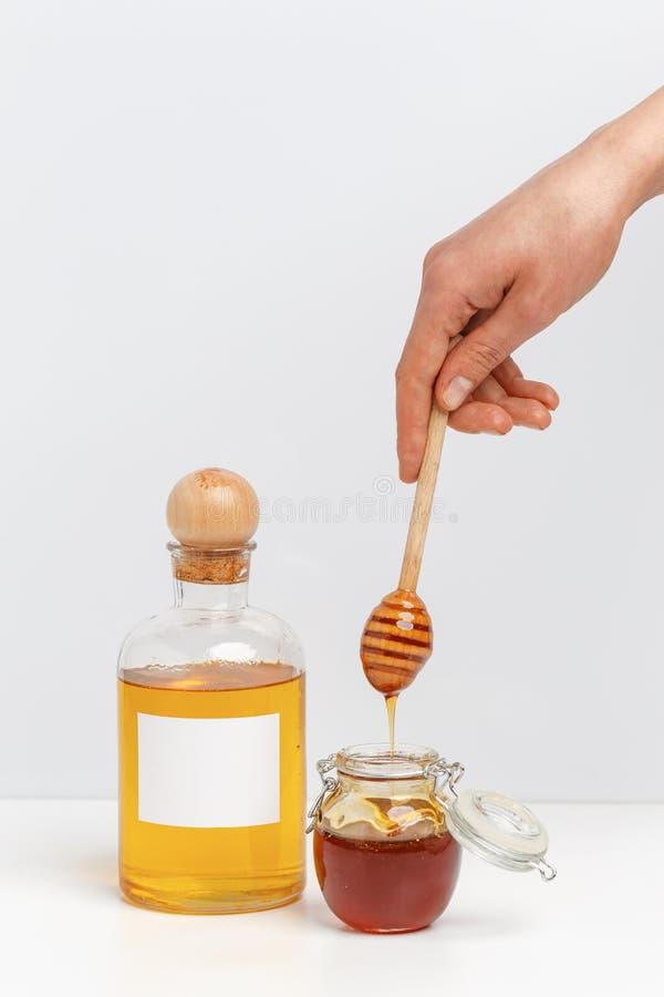 Exponeringsglaskrus med honung och träskeden på en vit bakgrund royaltyfri bild