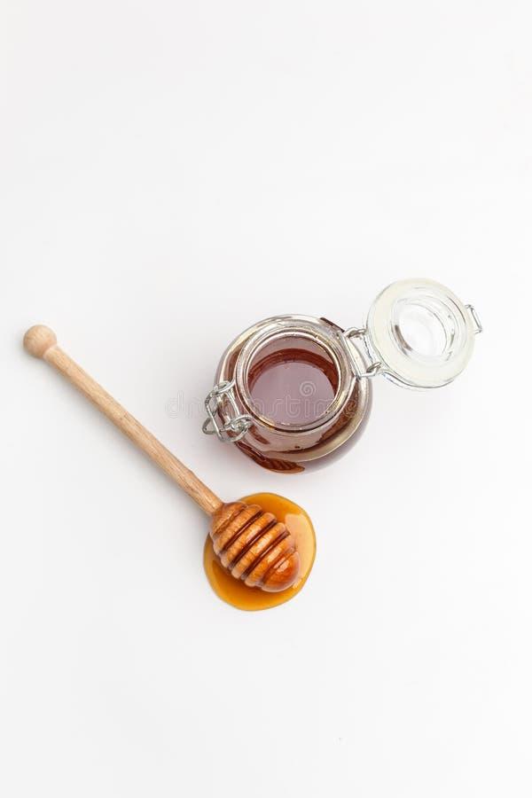 Exponeringsglaskrus med honung och träskeden på en vit bakgrund Top beskådar kopiera avstånd royaltyfri fotografi