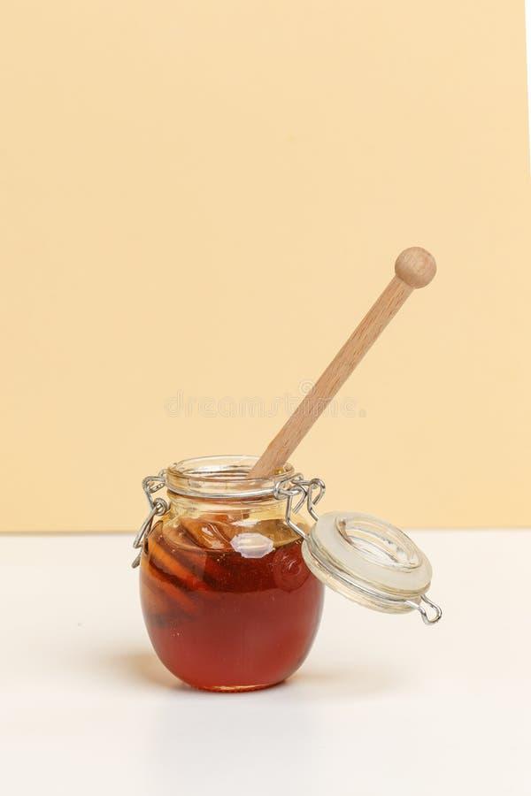 Exponeringsglaskrus med honung och träskeden på enguling bakgrund royaltyfri fotografi