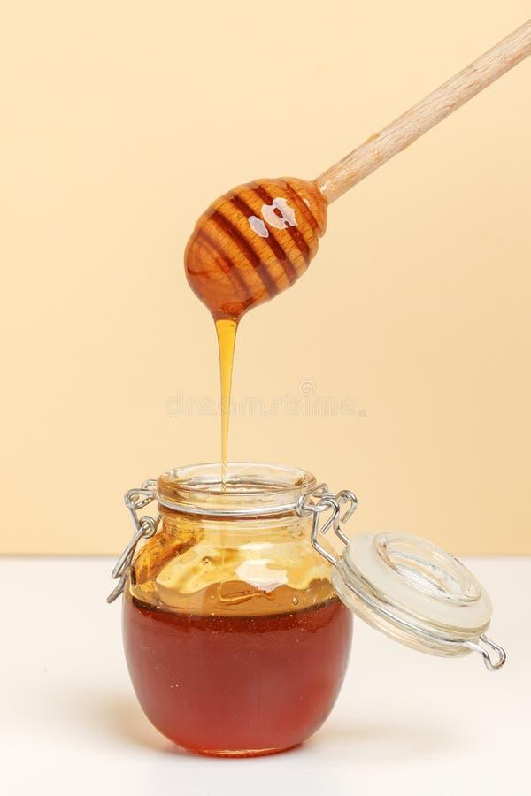 Exponeringsglaskrus med honung och träskeden på enguling bakgrund fotografering för bildbyråer