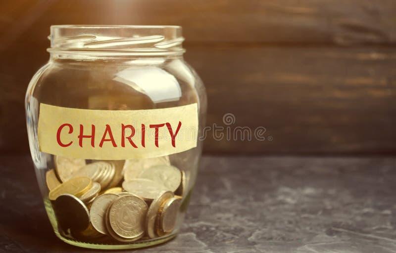 Exponeringsglaskrus med mynt och ordvälgörenheten Begreppet av att ackumulera pengar för donationer sparande Social medicinsk hjä fotografering för bildbyråer