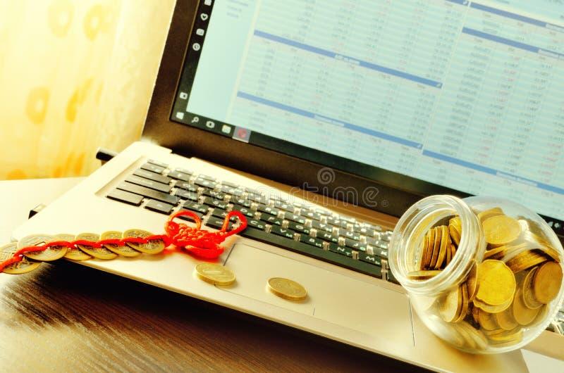 Exponeringsglaskrus med mynt på bärbara datorn arkivfoto