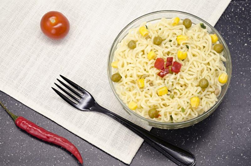 Exponeringsglasplatta av nudlar, gaffeln, röd peppar och tomaten fotografering för bildbyråer