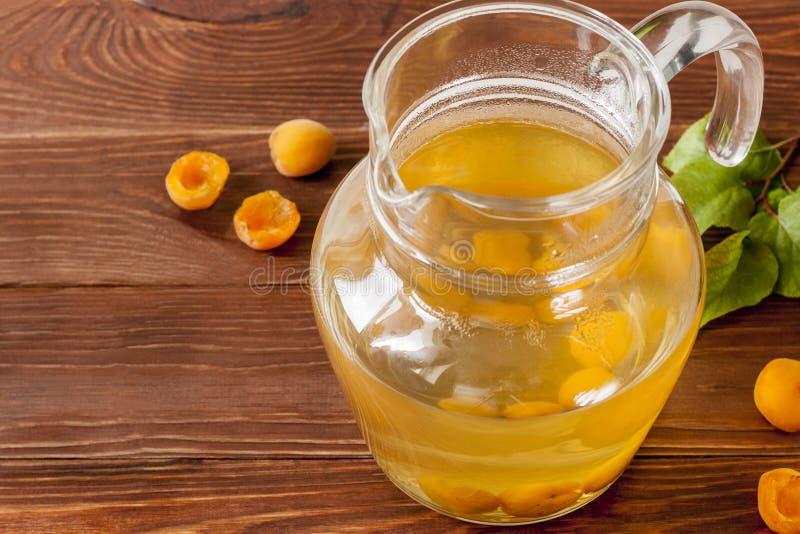 Exponeringsglastillbringare med aprikoskompott och mogna aprikors på en trätabell S?t och sund efterr?tt kopiera avst?nd royaltyfri bild