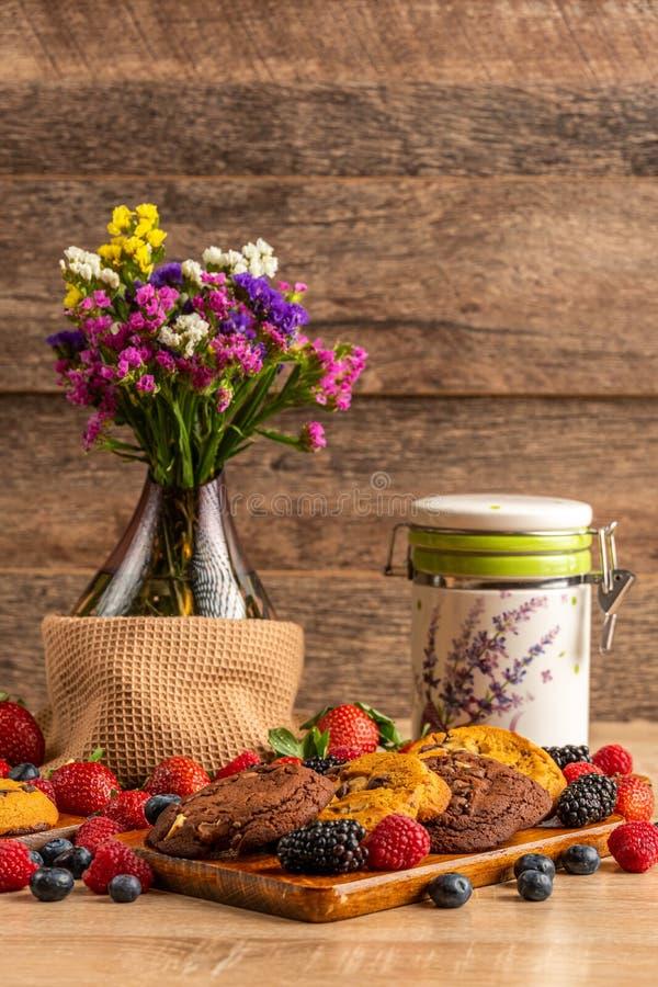 Exponeringsglasvas med blommor, den keramiska kruset och lösa bär arkivbilder