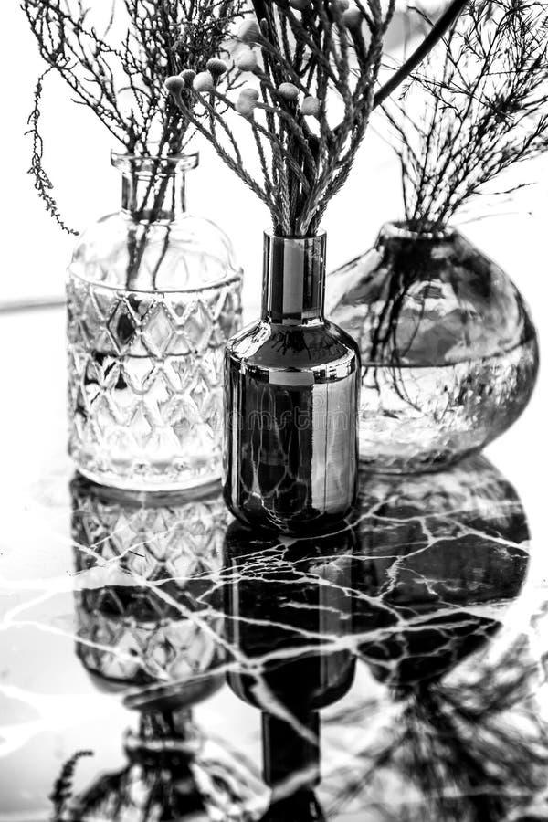 Exponeringsglasvaser med blommor marmorerar på tabellen fotografering för bildbyråer
