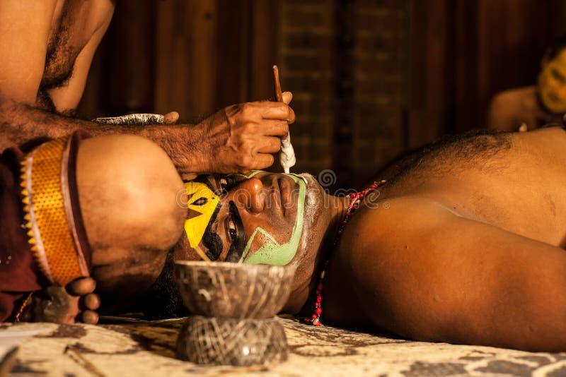 Exposant de Kathakali se préparant à la représentation en appliquant le maquillage de visage photo libre de droits