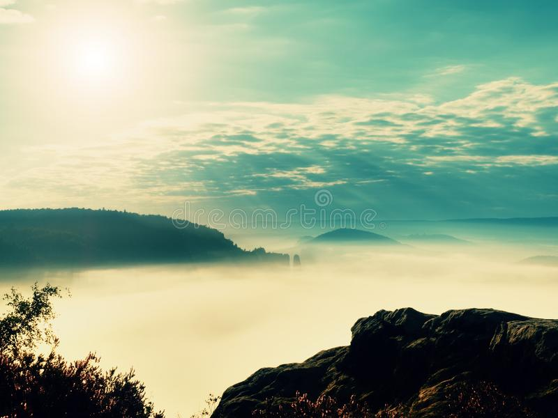 Exposed sandstone cliff above deep misty valley at the end of summer. Dreamy mood royalty free stock photography