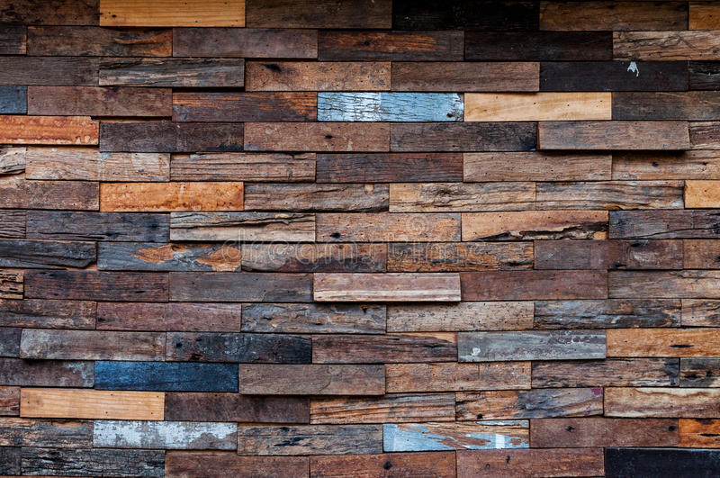 Exposed wooden wall exterior, patchwork of raw wood forming a beautiful parquet wood pattern. Wood wall pattern royalty free stock photo