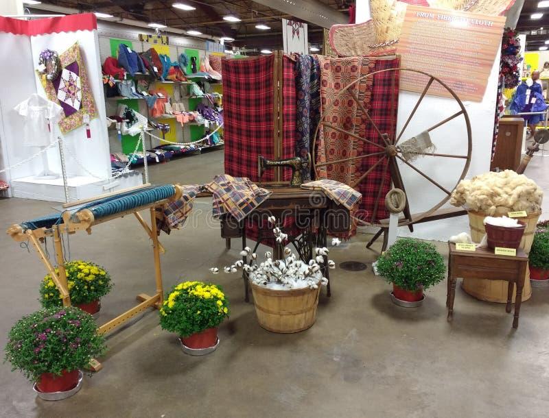 Exposição antiquado de matérias têxteis que caracteriza o algodão, um tear, a roda de giro, e a máquina de costura em uma feira d fotografia de stock royalty free