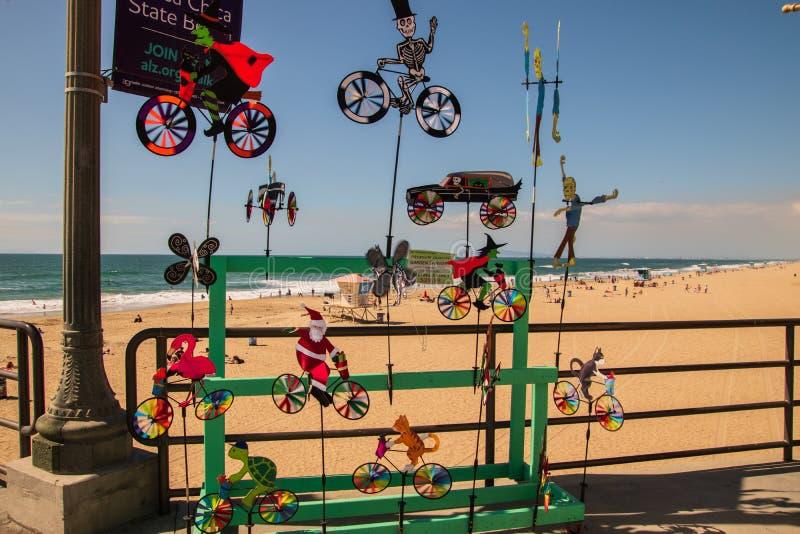 Exposição colorida dos giradores do vento que eram vendidos no cais do Huntington Beach com a praia e no oceano no fundo fotos de stock