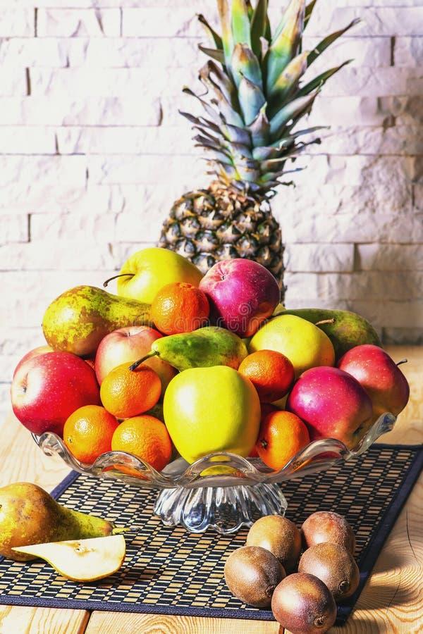 Exposição de frutos frescos, abacaxi, maçã verde e vermelha, quivi, mandarino, pera na tabela de madeira e fundo branco da parede foto de stock