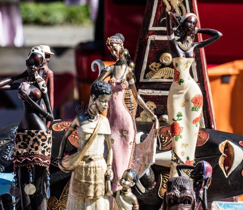 Exposição de várias estatuetas africanas das mulheres e de bonecas pretas para a decoração foto de stock