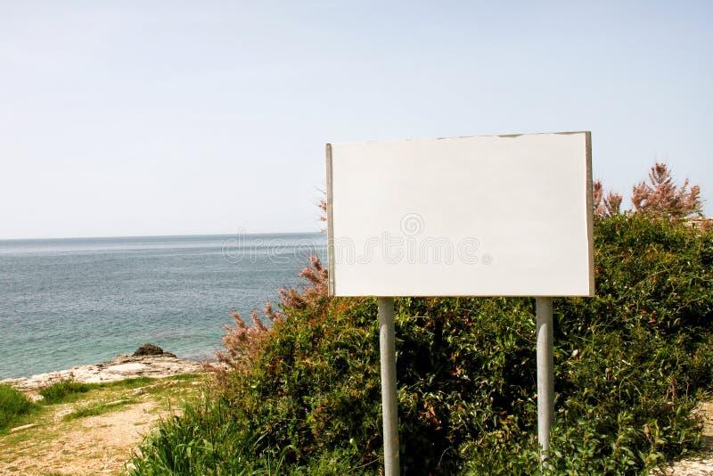 Exposição do quadro de avisos de anúncio e tabela vazias, mar no fundo Agências de propaganda imagem de stock royalty free