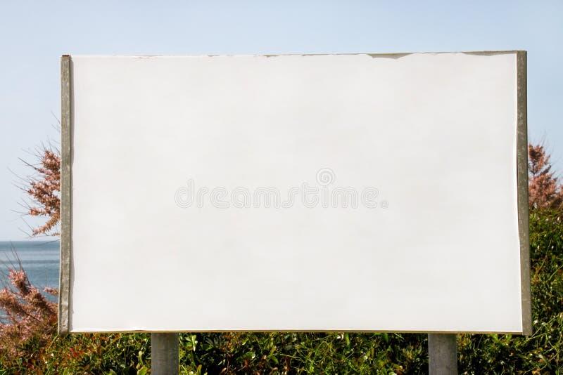Exposição do quadro de avisos de anúncio e tabela vazias, mar no fundo Agências de propaganda imagens de stock