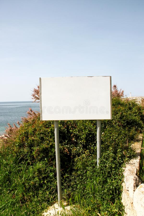 Exposição do quadro de avisos de anúncio e tabela vazias, mar no fundo Agências de propaganda foto de stock