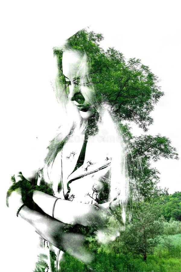 Exposição dobro da menina bonita nova entre as folhas e as árvores O retrato da senhora atrativa combinou com a fotografia da árv ilustração royalty free