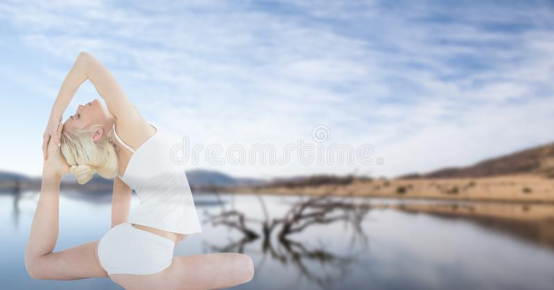 Exposição dobro da mulher bonita que faz a ioga e o lago contra o céu imagem de stock
