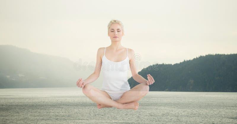 Exposição dobro da mulher que medita sobre o lago fotografia de stock
