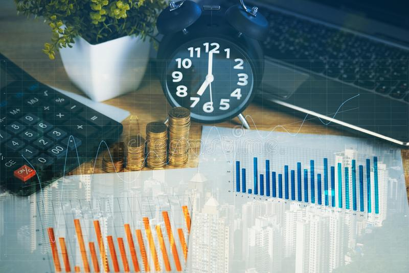 Exposição dobro da pilha da moeda com calculadora e despertador do caderno no fundo da cidade da tabela de funcionamento, conceit imagens de stock royalty free