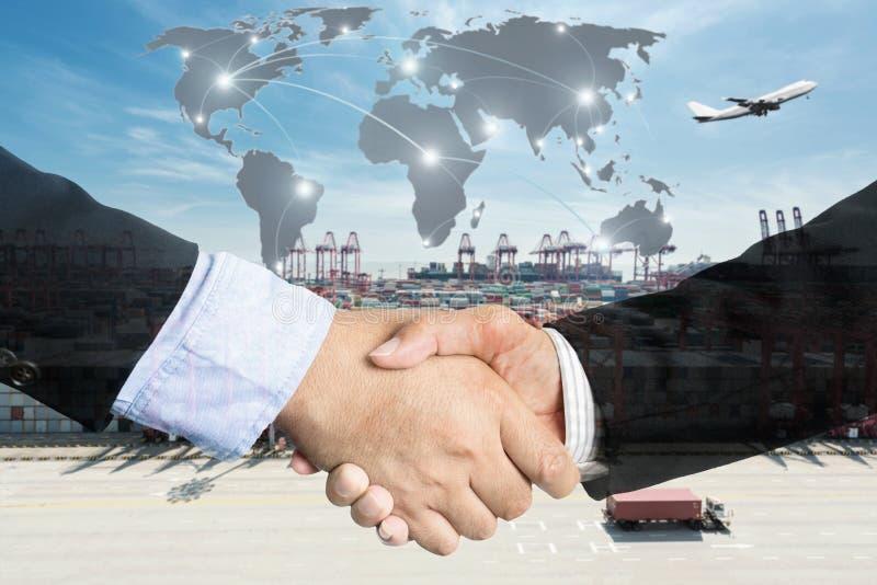 Exposição dobro de um aperto de mão do homem de negócios com a peça global do mapa fotografia de stock