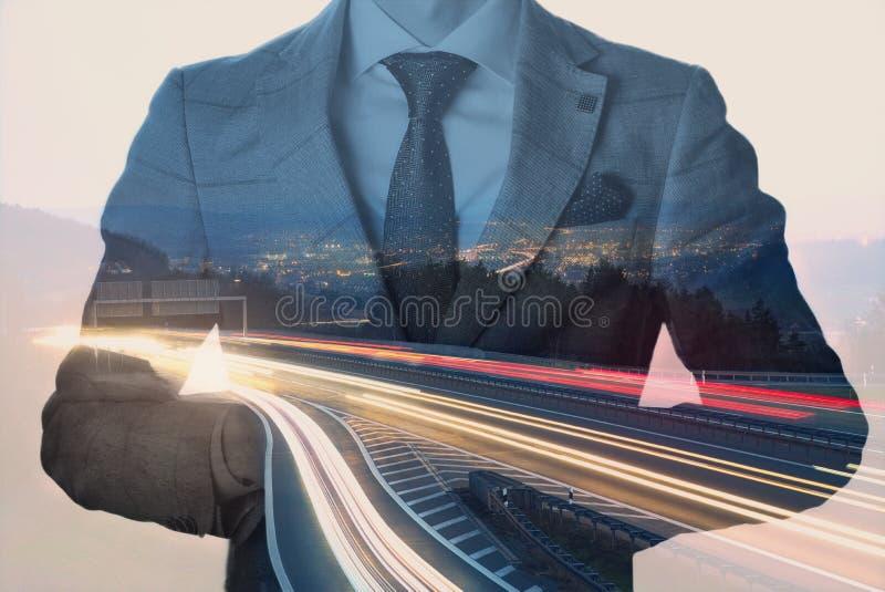 Exposição dobro de um homem de negócios com uma arquitetura da cidade no crepúsculo e nos lighttrails Cores vívidas e vintage ton foto de stock