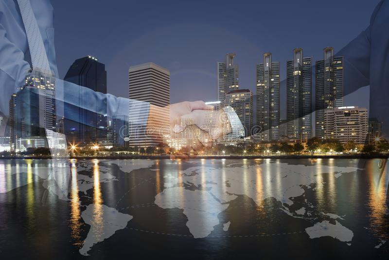 Exposição dobro do aperto de mão do homem de negócios na noite da arquitetura da cidade com fotografia de stock royalty free