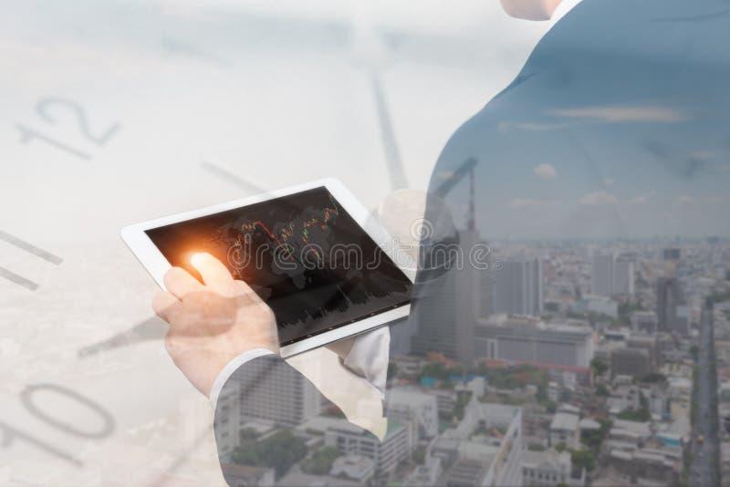 Exposição dobro do homem de negócios que usa a tabuleta com arquitetura da cidade foto de stock