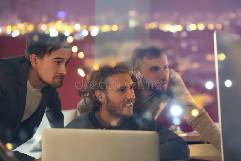 Exposição dobro dos homens que trabalham no escritório e na cidade iluminada na noite foto de stock