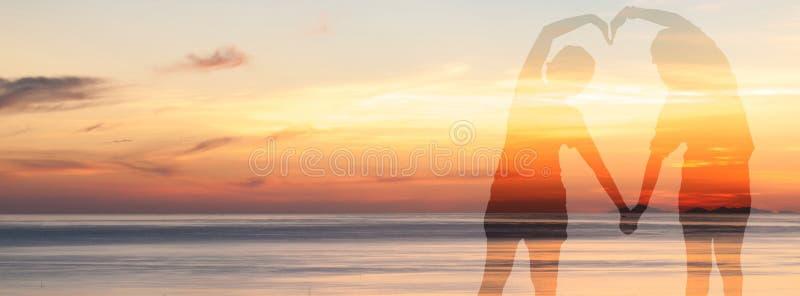A exposição dobro dos pares faz uma forma do coração com seu corpo sobre o mar no tempo crepuscular do céu imagens de stock royalty free