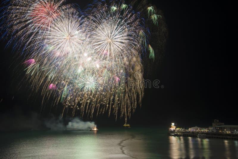 Exposição impressionante dos fogos-de-artifício sobre o mar com cais e barcos no wate foto de stock