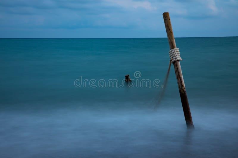Exposição longa da água do mar com logs e corda de madeira, no céu nebuloso fotos de stock