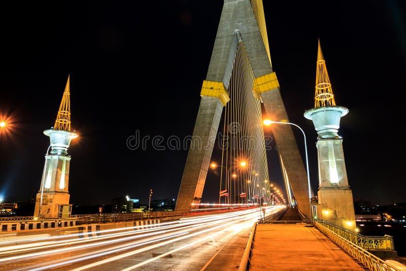 Exposição longa da luz do feixe na estrada na ponte de Rama 8, Bangk foto de stock