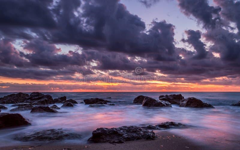 A exposição longa disparou do por do sol na praia com rochas e nuvens Corfu sul Grécia fotografia de stock royalty free