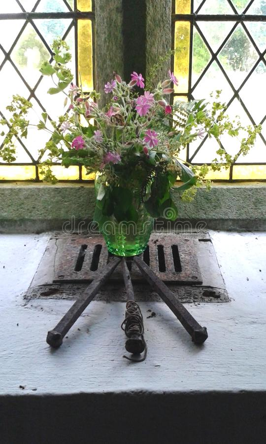 Exposição simbólica de flores selvagens e de pregos da crucificação, em uma janela da igreja, Inglaterra imagens de stock