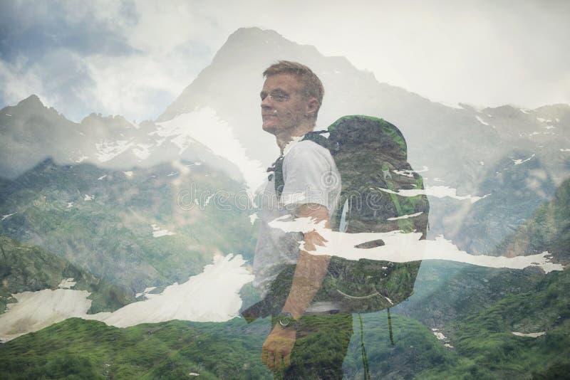 Exposición doble con el turista y las montañas foto de archivo