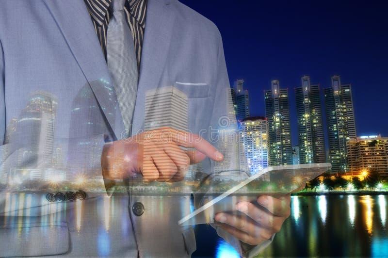 Exposición doble de la ciudad y del hombre de negocios que usa la tableta digital foto de archivo libre de regalías
