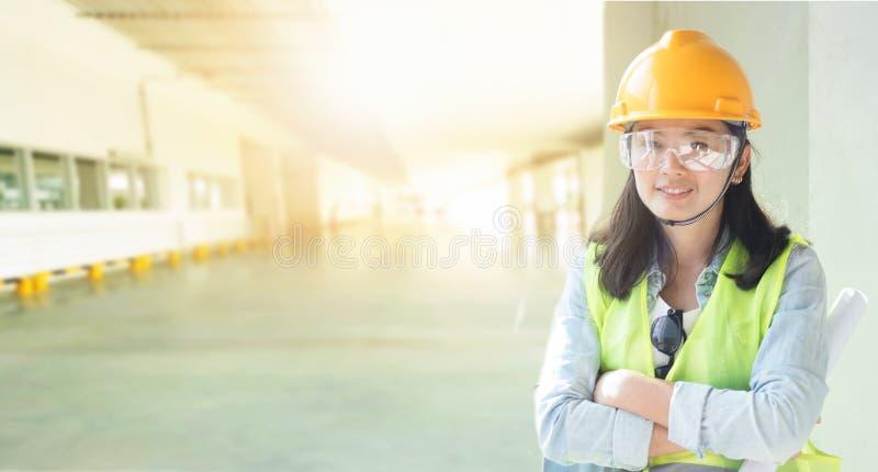 Exposición doble de la ingeniería de la mujer que lleva el casco amarillo imagenes de archivo