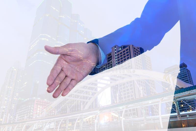 Exposición doble de la mano que extiende del hombre de negocios a la sacudida con el fondo de la ciudad imágenes de archivo libres de regalías