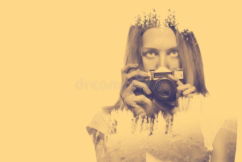 Exposición doble de la mujer joven que celebra el viejo fondo de la cámara y de la naturaleza fotos de archivo
