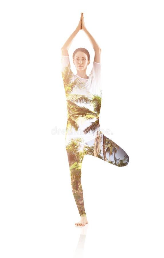 Exposición doble de la mujer que hace ejercicio de la yoga fotos de archivo