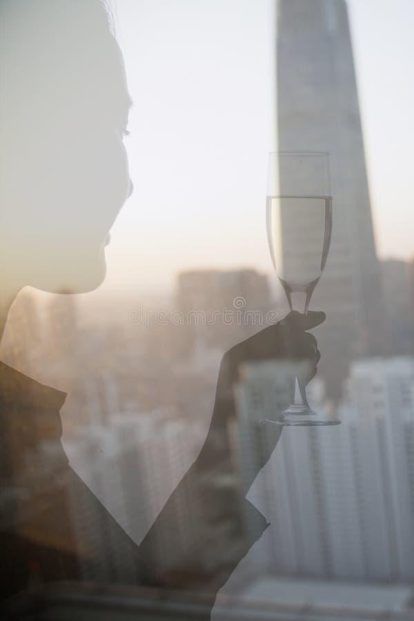 Exposición doble de la mujer que tuesta con la flauta de champán sobre paisaje urbano, Pekín, China fotografía de archivo