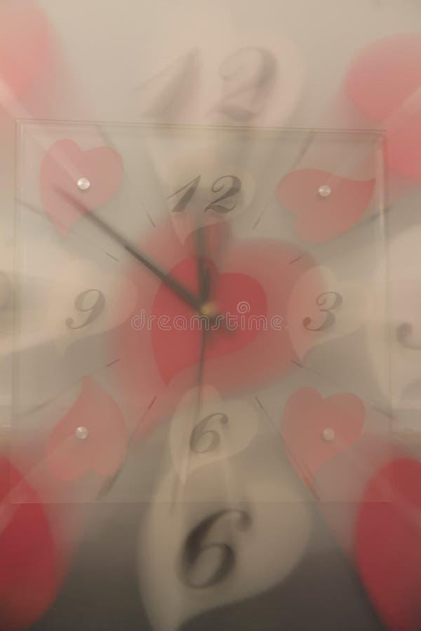 Exposición doble de un reloj con los corazones blancos y rojos imágenes de archivo libres de regalías