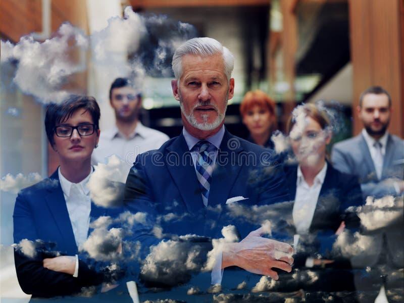 Exposición doble del hombre de negocios mayor con su equipo en la oficina fotos de archivo