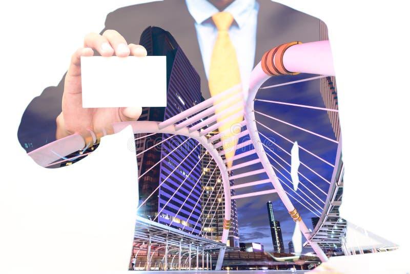 Exposición doble del hombre de negocios que celebra o que muestra la tarjeta de visita y el fondo en blanco de la ciudad foto de archivo