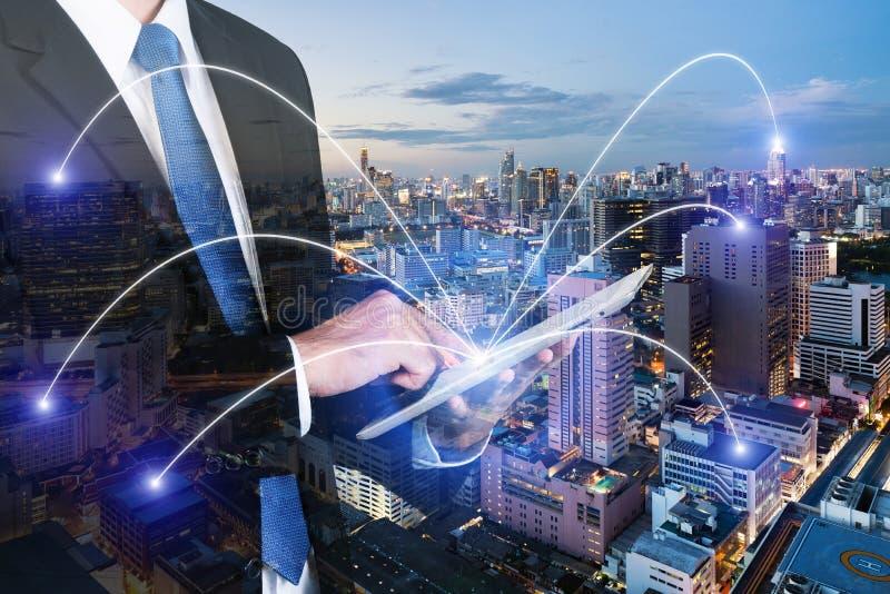 Exposición doble del hombre de negocios usando la PC digital de la tableta con el netw fotografía de archivo