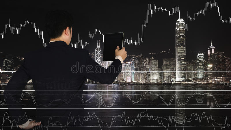 Exposición doble del hombre de negocios usando la tableta con el gráfico financiero imagen de archivo
