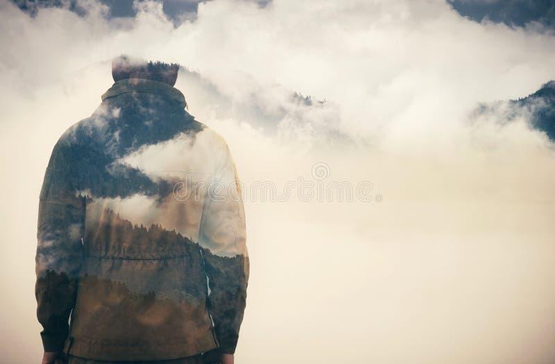 Exposición doble del hombre y del bosque nublado de las montañas fotografía de archivo libre de regalías
